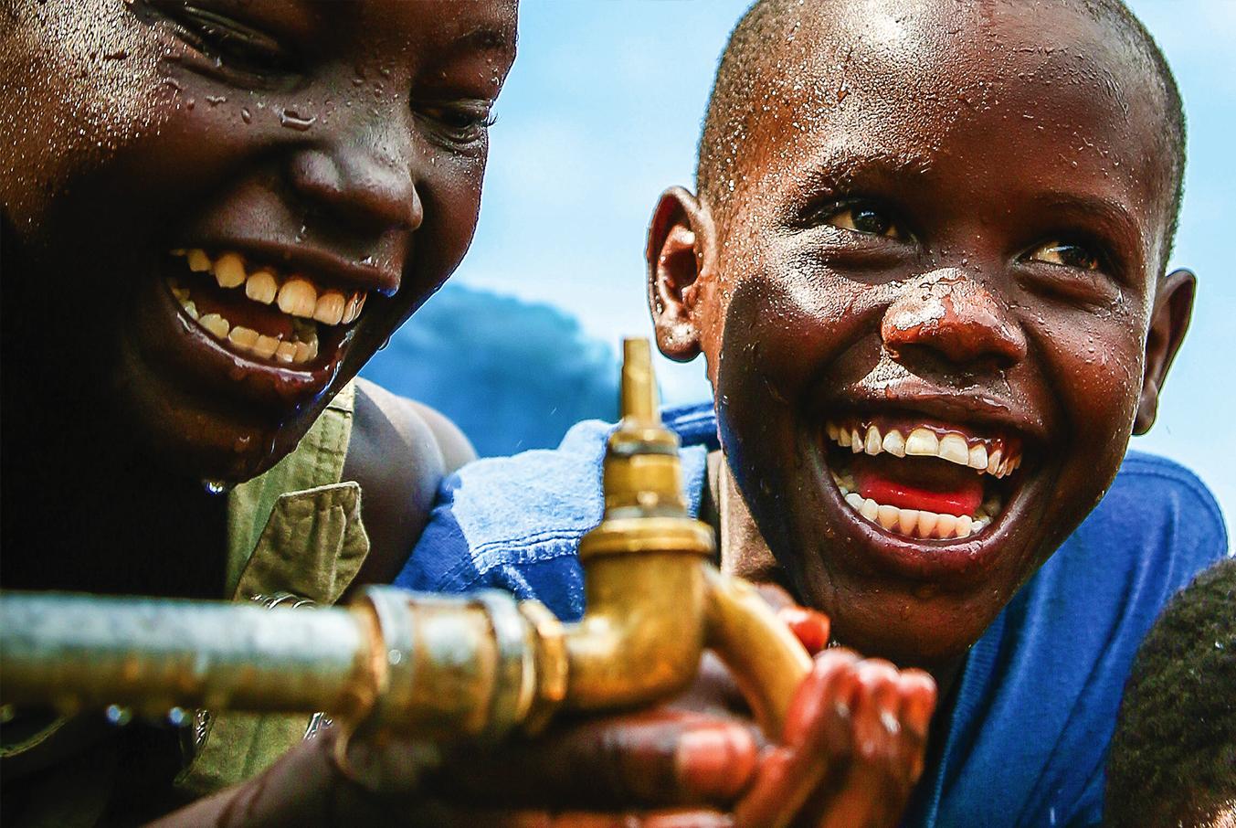 Twee jongens bij waterpunt in Afrika